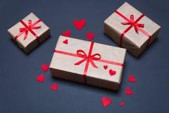 As caixas de presente decoradas com as fitas vermelhas com curvas encontram-se em um fundo preto Fotografia de Stock Royalty Free