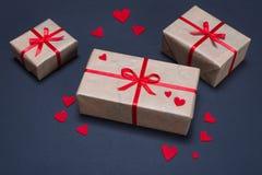 As caixas de presente decoradas com as fitas vermelhas com curvas encontram-se em um fundo preto Fotografia de Stock
