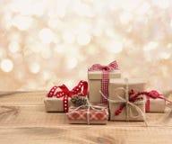 As caixas de presente do Natal na tabela de madeira sobre o sumário iluminam o fundo Fotos de Stock Royalty Free