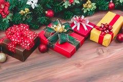 As caixas de presente festivas alinham na placa de madeira, decoram com sutiã do pinho foto de stock