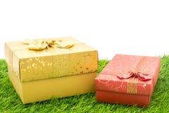 As caixas de presente na terra da grama verde Fotografia de Stock