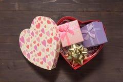 As caixas de presente roxas e cor-de-rosa estão na caixa vermelha do coração, no b de madeira fotografia de stock royalty free