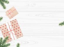 As caixas de presentes com abeto ramificam no fundo de madeira branco Vista superior Foto de Stock