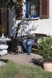 as calças de brim da interrupção decoradas com as flores que sentam-se em um jardim bench a Foto de Stock Royalty Free