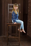 As calças de brim da menina e a camisa azul estão sentando-se em uma cadeira alta na sala com paredes marrons Fotografia de Stock