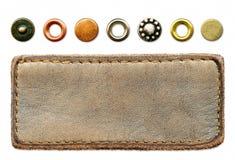 As calças de brim de couro etiquetam e um jogo dos rebites do metal Imagens de Stock Royalty Free