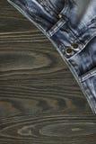 As calças de brim desvanecidas velhas que encontram-se no canto de um fundo de madeira Fotos de Stock Royalty Free