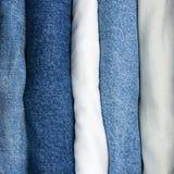 As calças de brim empilham, detalharam o close up macro vertical, sarja de Nimes azul do índigo, cáqui, bege branco Imagem de Stock Royalty Free