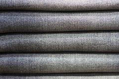 As calças de brim empilharam o close-up, textura, fundo fotografia de stock royalty free