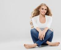 As calças de brim louras do cabelo encaracolado da mulher bonita formam o comprimento completo que senta-se no assoalho fotografia de stock