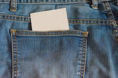 As calças de brim pocket com um cartão vazio nele Fotografia de Stock Royalty Free