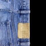 As calças de brim texture com a etiqueta de couro fundo preto isolado fotografia de stock royalty free