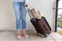 As calças de brim vestindo da jovem mulher levam um saco da bagagem Conceito do curso e do internamento imagem de stock