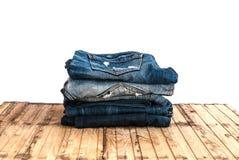 As calças de calças de ganga rolam isolado acima na madeira Imagem de Stock