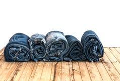 As calças de calças de ganga rolam isolado acima na madeira Imagem de Stock Royalty Free
