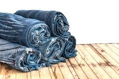 As calças de calças de ganga rolam isolado acima na madeira Foto de Stock Royalty Free