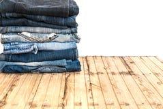 As calças de calças de ganga rolam isolado acima na madeira Fotos de Stock