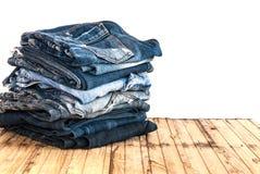 As calças de calças de ganga rolam isolado acima na madeira Fotografia de Stock