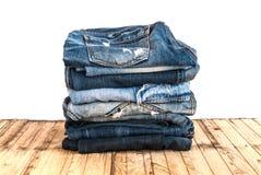 As calças de calças de ganga rolam isolado acima na madeira Imagens de Stock