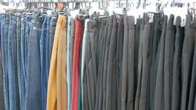 As calças penduram no gancho, as mulheres olham a roupa e escolhem-na Feira da ladra, roupa vendida no mercado vídeos de arquivo