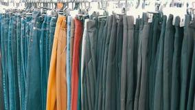 As calças penduram no gancho, as mulheres olham a roupa e escolhem-na Feira da ladra, roupa vendida no mercado filme