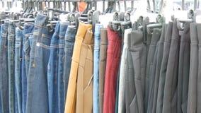 As calças penduram no gancho, as mulheres olham a roupa e escolhem-na Feira da ladra, roupa vendida no mercado video estoque