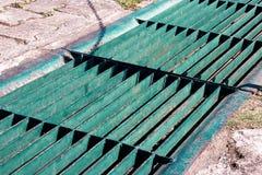As calhas drenam a grelha, tampa do dreno Drenos da estrada - tampa do esgoto Grelha do ferro do dreno da água na estrada em cada imagens de stock royalty free