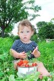 As camas do jardim perto da menina estão sentando-se, e próximo é Foto de Stock