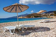 As camas e os guarda-sóis de Sun em um mar vazio encalham nos seixos pitorescos do mediterrâneo Foto de Stock Royalty Free