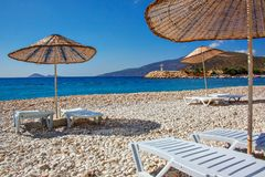 As camas e os guarda-sóis de Sun em um mar vazio encalham nos seixos pitorescos do mediterrâneo Fotos de Stock Royalty Free
