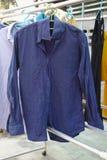 As camisas azuis penduram seco a roupa na linha de roupa imagens de stock royalty free