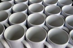 As canecas de café branco arranjam em um hotel para o serviço imagens de stock