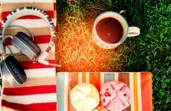 As canecas de café preto colocam na grama com doces dos doces, com um mus Fotos de Stock Royalty Free