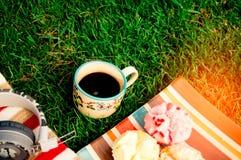 As canecas de café preto colocam na grama com doces dos doces, com um mus Fotografia de Stock