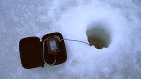 As capturas do pescador pescam com um receptor acústico de eco do inverno no furo filme
