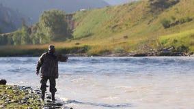 As capturas do pescador pescam contra o contexto de uma paisagem da montanha rugidos do turista do pescador em um rio da montanha video estoque