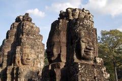 As caras antropomórficas cinzelaram na pedra no Bayon Wat na luz do fim da tarde, um templo do século XII dentro de COM de Angkor foto de stock royalty free