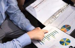 As cartas e os gráficos de negócio centram-se sobre apontar os dedos Fotos de Stock Royalty Free