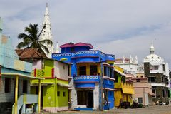 As casas coloridas brilhantes dos pescadores aproximam a igreja colonial Imagem de Stock
