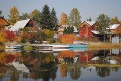 As casas de campo do verão são refletidas na água Fotos de Stock
