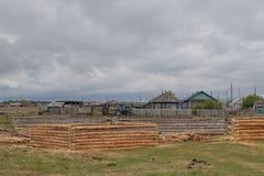 As casas de log do pinho entram o prado Logs cancelados da casca fotografia de stock