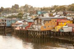As casas de madeira tradicionais construídas em pernas de pau ao longo das águas afiam em Castro, Chiloe no Chile imagem de stock