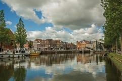 As casas do tijolo, os barcos amarrados e a ponte de bascule refletiram na superfície larga da água do canal no por do sol em Wee fotos de stock