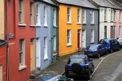 As casas e os carros coloridos estacionaram na frente deles, Augustine Place, quintilha jocosa, Irlanda, queda, 2014 fotografia de stock royalty free