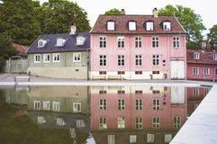 As casas velhas do rosa e do verde refletiram em uma lagoa fotos de stock