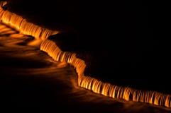 As cascatas pequenas iluminaram-se acima com luzes alaranjadas na noite Fotos de Stock