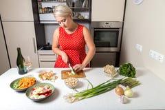 As cebolas do corte da menina no vermelho pontilhado vestem-se na cozinha Fotografia de Stock Royalty Free