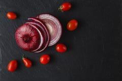 As cebolas vermelhas circundam com os tomates na placa da ardósia Fotos de Stock
