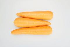 As cenouras alaranjadas frescas postas arranjam em uma tabela branca Foto de Stock Royalty Free