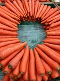 As cenouras alaranjadas suculentas arranjaram em um círculo em uma tabela de madeira fotos de stock
